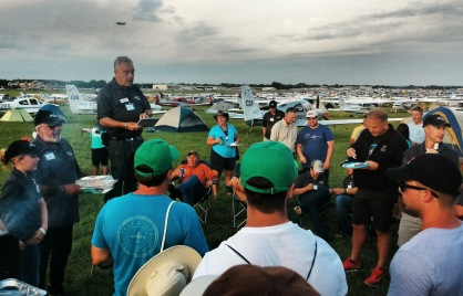 Leader of the C2A Fly-In, Mike Randomsky, giving away raffle prizes. Appropriately, a Cirrus is flying over his head in this picture!